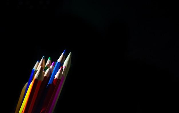 Fournitures scolaires de crayons de couleur dans une rangée, isolée sur un fond noir.