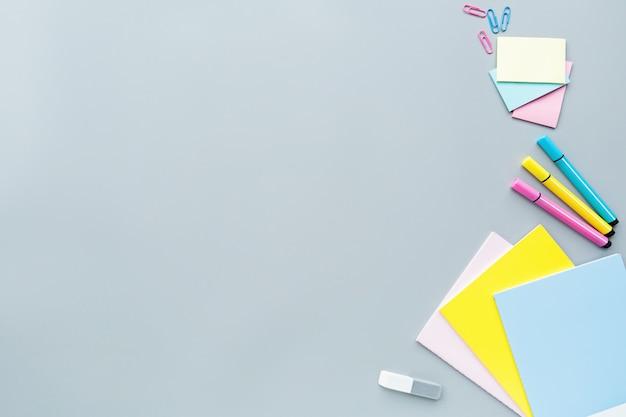 Fournitures scolaires, crayons de couleur, pinces, papier sur fond gris