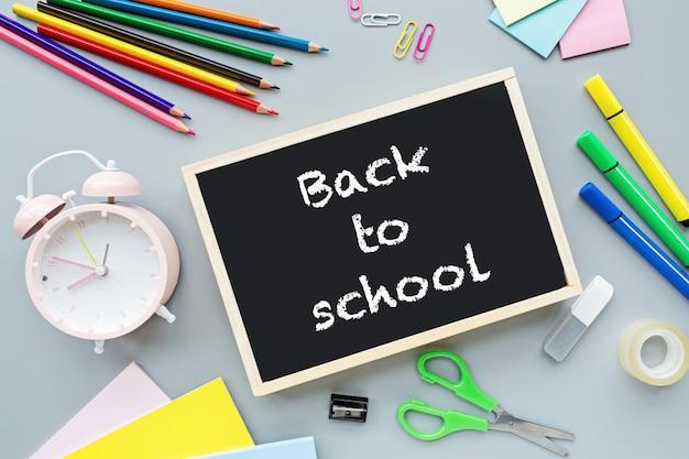 Fournitures scolaires, crayons de couleur, pinces, réveil, papier sur fond gris