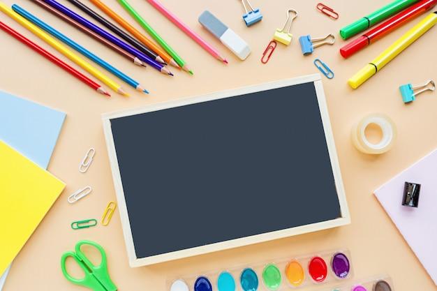 Fournitures scolaires, crayons, peintures, papier sur fond orange pastel