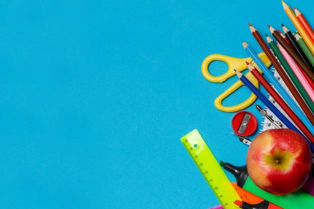 Fournitures scolaires double bordure contre un fond de papier bleu