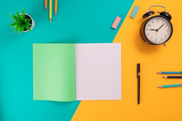 Fournitures scolaires sur fond bleu et jaune avec la place pour le texte.