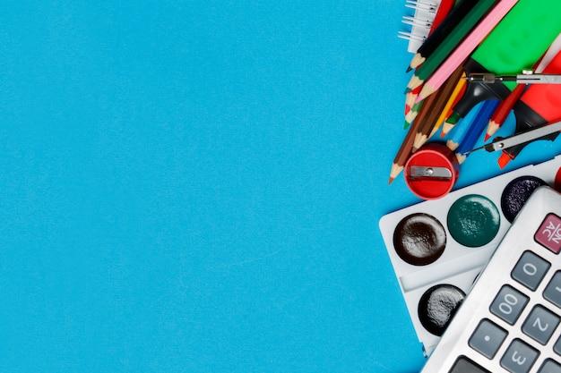 Fournitures scolaires sur fond bleu prêt pour votre conception. vue de dessus