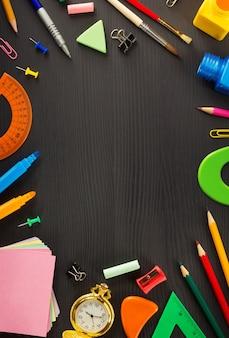 Fournitures scolaires sur fond de bois noir