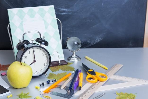 Fournitures scolaires sur le fond du tableau des enseignants