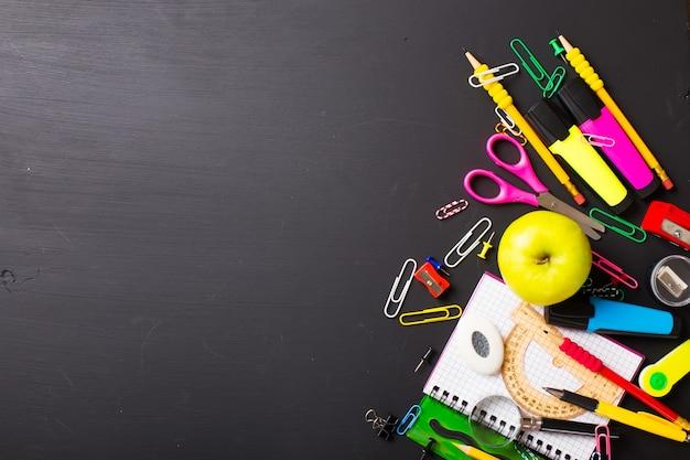 Fournitures scolaires sur fond noir. disposition plate.