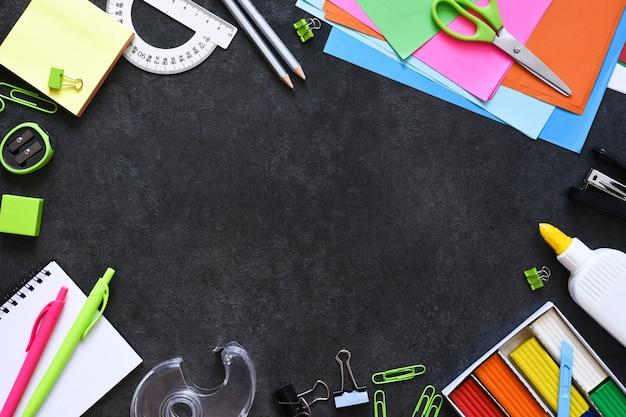 Fournitures scolaires sur fond noir. retour au concept de l'école. composition à plat avec papeterie scolaire.