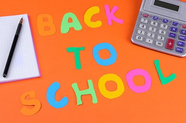 Fournitures scolaires sur fond orange vif avec l'inscription de retour à l'école.