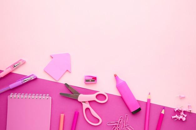 Fournitures scolaires sur fond rose avec espace de copie. retour à l'école. mise à plat.