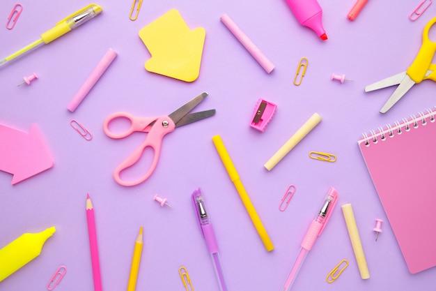 Fournitures scolaires sur fond rose. retour à l'école. mise à plat. minimalisme