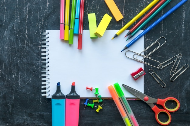 Fournitures scolaires sur un fond de tableau. espace libre pour le texte