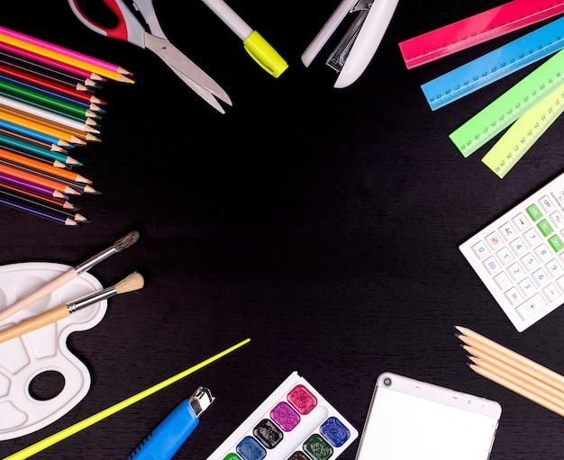 Fournitures scolaires sur fond de tableau noir. concept de retour à l'école