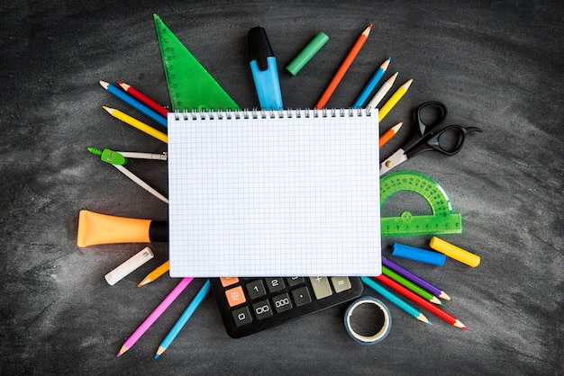 Fournitures scolaires sur fond de tableau noir. crayons de couleur, calculatrice, règles et cahiers. retour au concept de l'école.