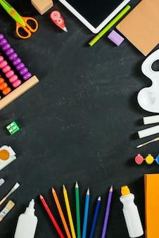 Fournitures scolaires sur fond de tableau noir. retour au concept de l'école. cadre, plat, espace de copie pour le texte