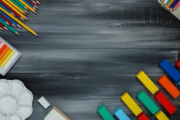 Fournitures scolaires sur fond de tableau noir. retour au concept de l'école.