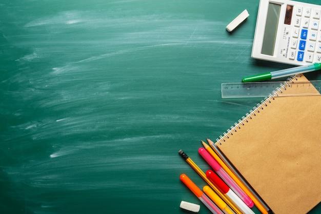 Fournitures scolaires sur fond de tableau