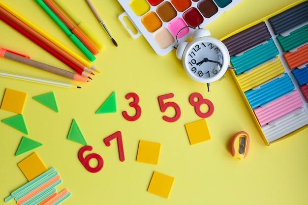 Fournitures scolaires sur jaune, stylo, crayons, marqueurs, aquarelles, pâte à modeler, taille-crayon, nombres, formes géométriques, bâtons de comptage, réveil, pâte à modeler, mise à plat