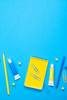 Fournitures scolaires jaunes sur le fond bleu pastel.