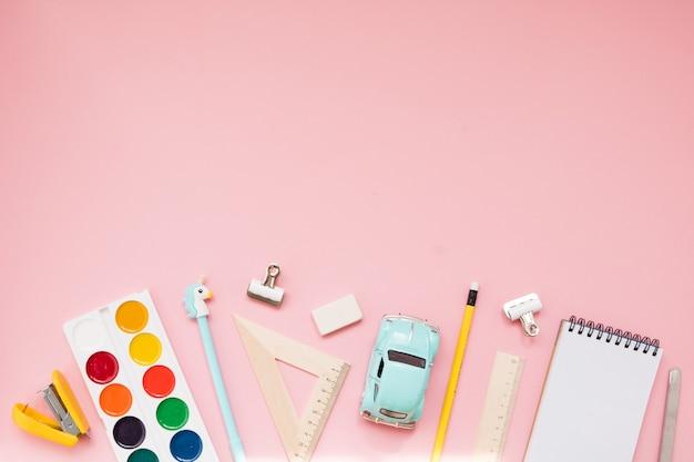 Fournitures scolaires jaunes sur fond rose pastel