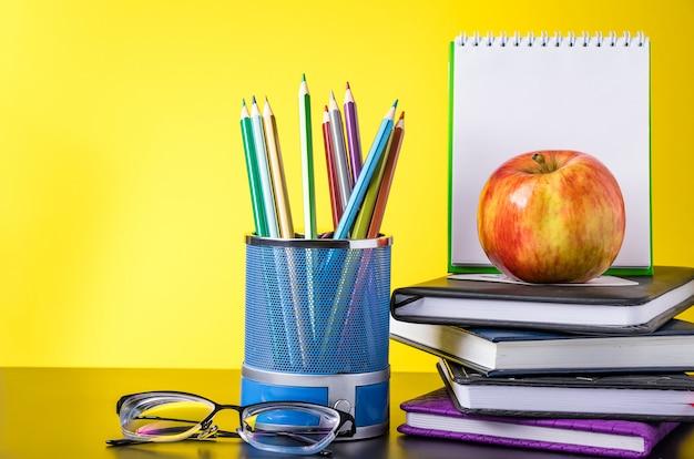 Fournitures scolaires et livres sur fond jaune.