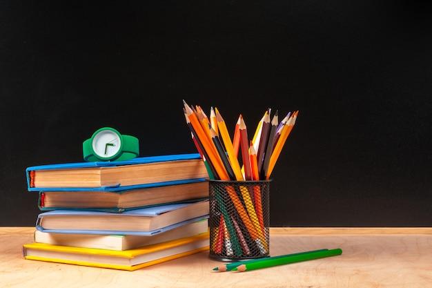 Fournitures scolaires et livres sur fond noir