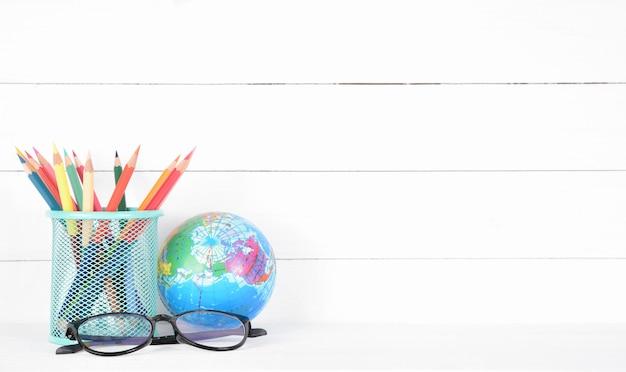 Fournitures scolaires, lunettes et globe sur bois blanc