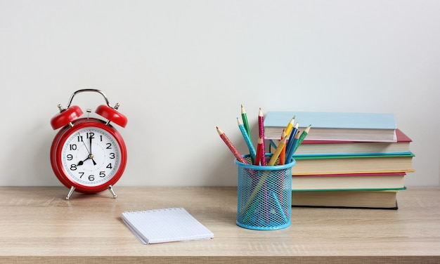 Fournitures scolaires manuels réveil et crayons de couleur sur la table