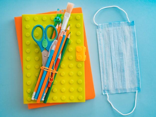 Fournitures scolaires avec masque médical sur bleu bleu. mise à plat, vue de dessus, mise en page, modèle, espace libre