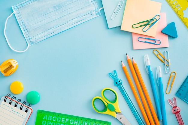Fournitures scolaires avec masque médical sur bleu. mise à plat, vue de dessus, mise en page, modèle, espace libre