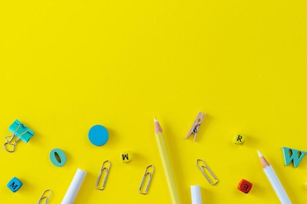 Fournitures scolaires multicolores sur fond jaune avec espace de copie