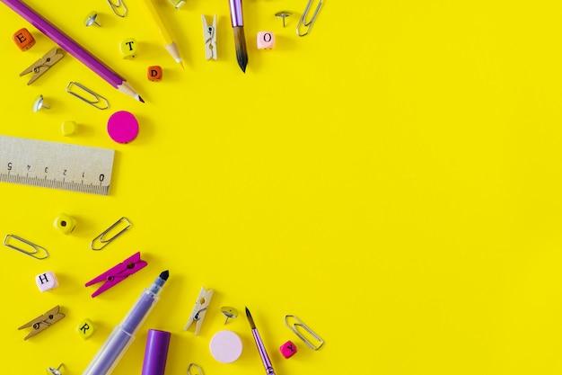 Fournitures scolaires multicolores sur fond jaune avec espace de copie.