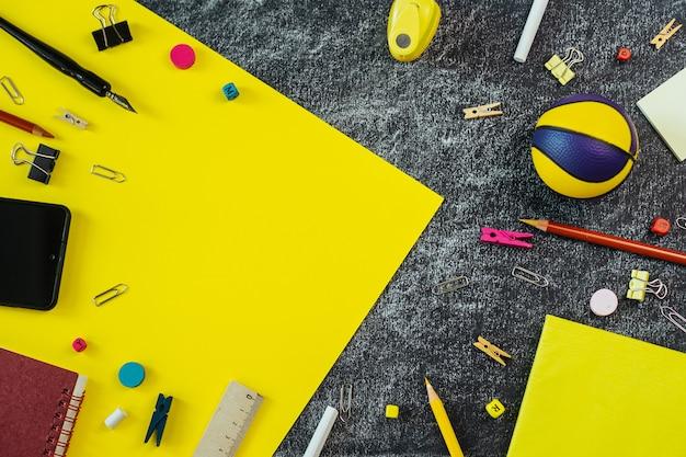 Fournitures scolaires multicolores sur fond de tableau noir et jaune avec espace de copie.