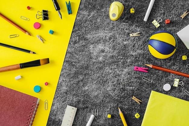 Fournitures scolaires multicolores sur fond de tableau noir et jaune.