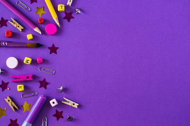 Fournitures scolaires multicolores sur fond violet avec espace de copie.
