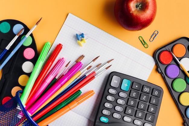 Fournitures scolaires multicolores et pomme rouge dispersés sur un bureau jaune