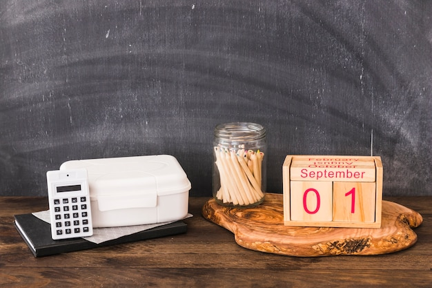 Fournitures scolaires et nourriture près du tableau