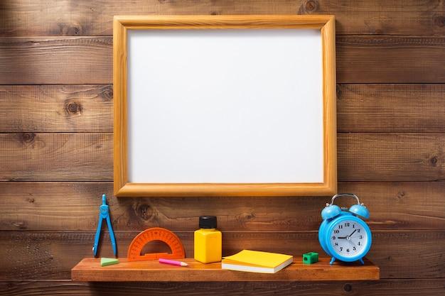 Fournitures scolaires et outils sur une étagère murale en bois