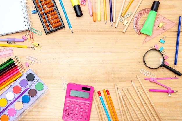 Fournitures scolaires et papeterie sur fond de table en bois