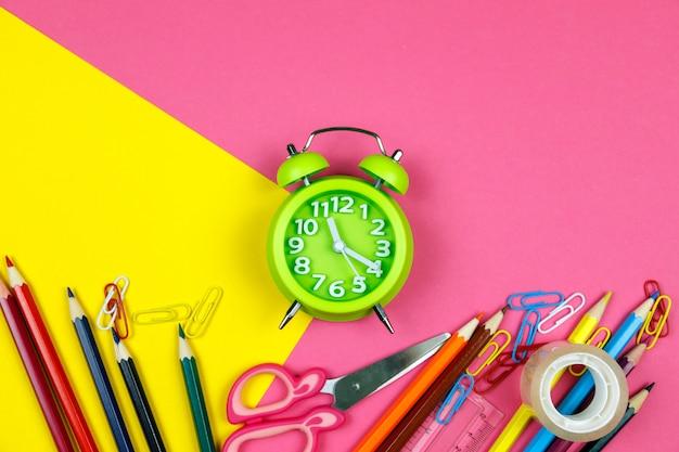 Fournitures scolaires sur papier rose et jaune