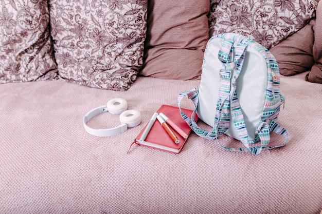 Fournitures scolaires à plat sur le canapé après l'école. sac à dos bleu, casque blanc, cahier et stylos.