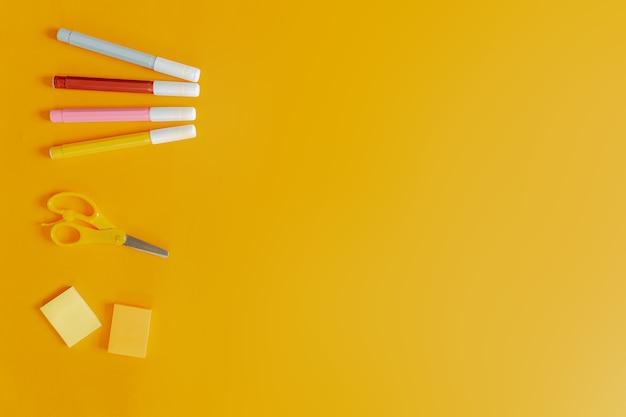 Fournitures scolaires à plat sur le fond orange. cahier rose et marqueurs colorés, ciseaux et autocollants.