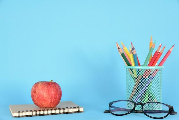 Fournitures scolaires, pomme, lunettes et livre sur bleu