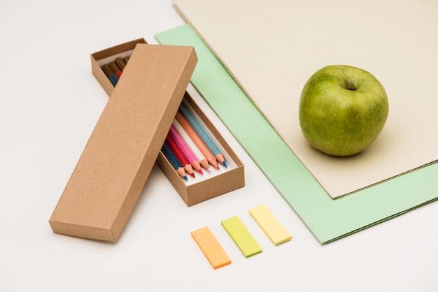 Fournitures scolaires et pomme sur tableau blanc