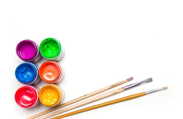 Fournitures scolaires. les pots avec de la peinture et des pinceaux d'art colorés sont sur un fond blanc.