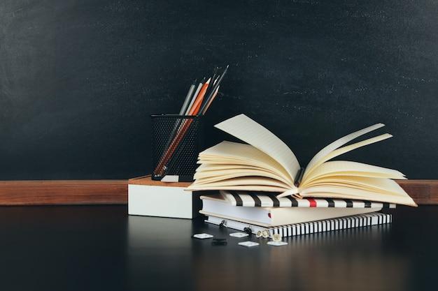 Fournitures scolaires près du tableau noir, gros plan