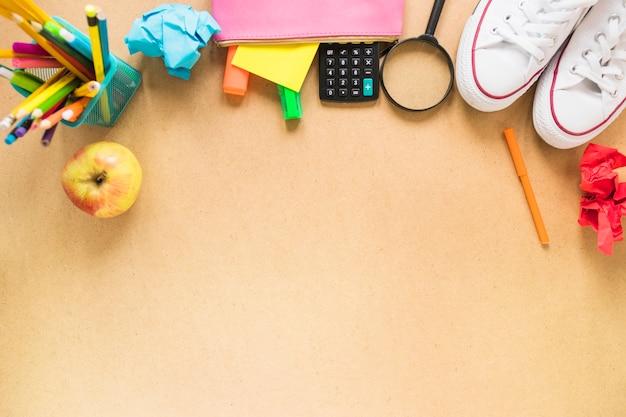 Fournitures scolaires près de pomme et de baskets