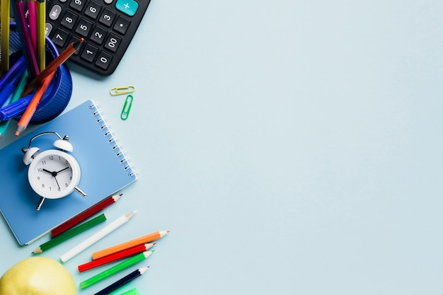 Fournitures scolaires et réveil disposés sur un bureau bleu