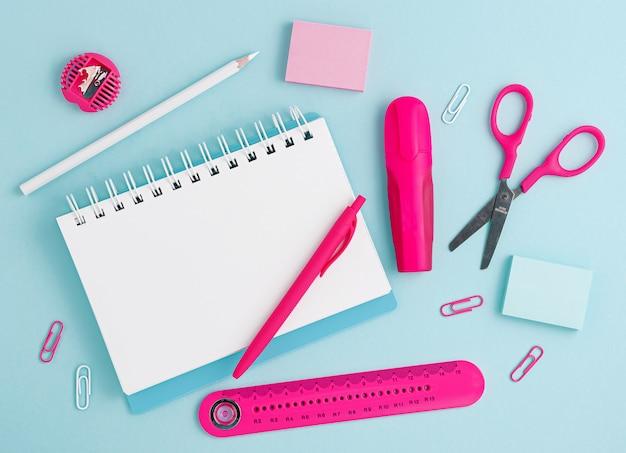 Fournitures scolaires roses et bloc-notes vide blanc sur fond bleu pastel. frais généraux, espace de copie