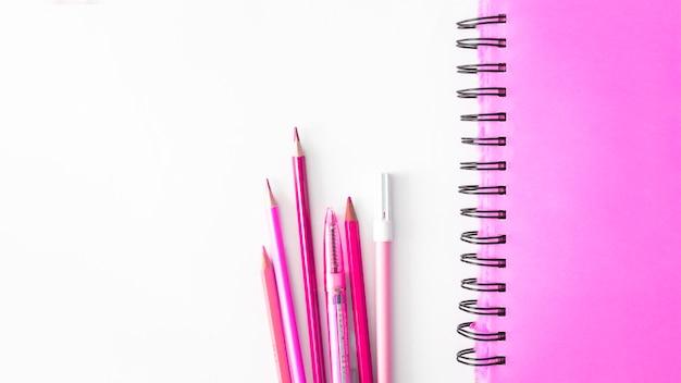 Fournitures scolaires roses sur un bureau blanc