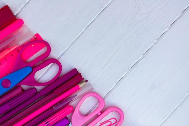 Fournitures scolaires roses sur un fond en bois blanc. vue de dessus. espace de copie. concept d'éducation et de retour à l'école.